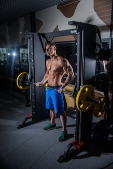 Wysportowany mężczyzna z dużymi mięśniami i szerokimi plecami trenuje na siłowni, fitness i napompowanej wyciskaniu brzucha. seksowny mężczyzna na siłowni z hantlami. rosja, swierdłowsk, 2 czerwca 2018 r.