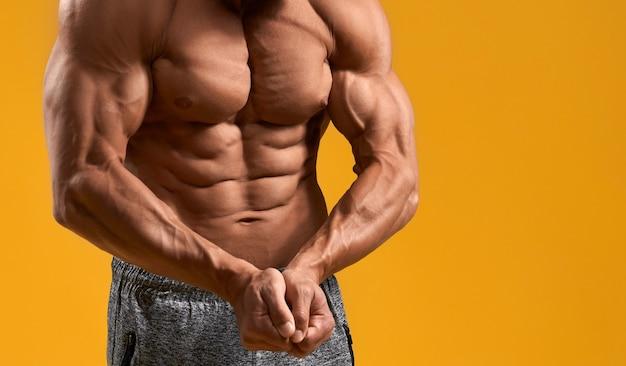 Wysportowany mężczyzna z nagim torsem pokazującym bicepsy