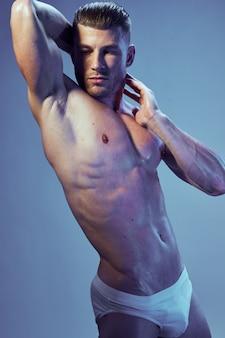 Wysportowany mężczyzna z umięśnionym ciałem, białą bielizną nagiego tułowia