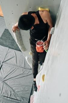 Wysportowany młody człowiek ćwiczący wspinaczkę w krytym centrum boulderingu ze sztucznymi skałami