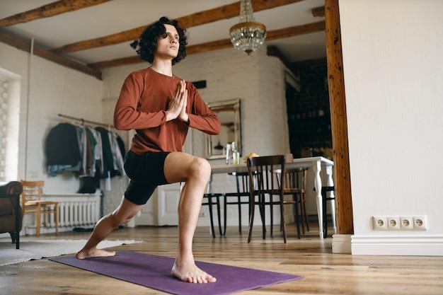Wysportowany młody jogin mężczyzna praktykujący jogę w pomieszczeniu, stojący boso na macie, trzymający się za ręce w namaste, wykonujący rano sekwencję powitania słońca.