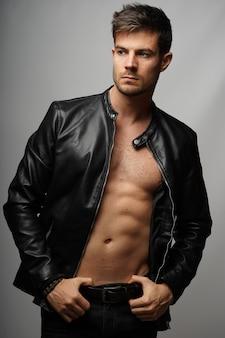 Wysportowany młody latynoski męski model ubrany w czarną skórzaną kurtkę i pozujący na szarej ścianie