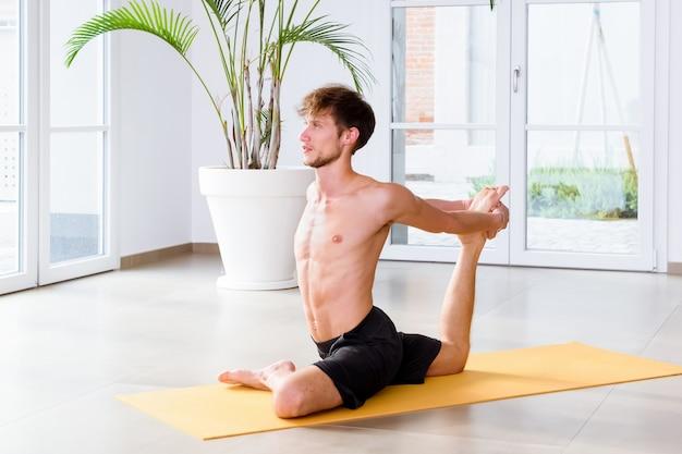 Wysportowany młody mężczyzna wykonujący pozę jogi eka pada kapotasna, aby rozprostować biodra