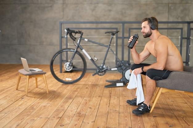 Wysportowany pan bez koszuli trzymający butelkę wody i ręcznik siedzący na krześle w pokoju z rowerem treningowym