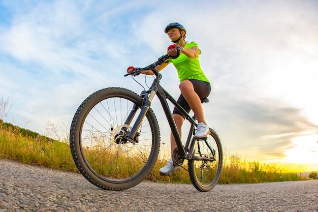 Wysportowany piękny rowerzysta jeździ na rowerze po drodze na tle przyrody