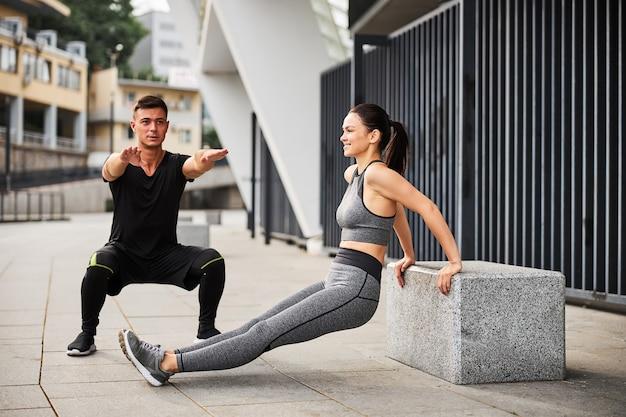 Wysportowany przystojny mężczyzna robi przysiady, podczas gdy jego dziewczyna robi pompki na triceps na świeżym powietrzu
