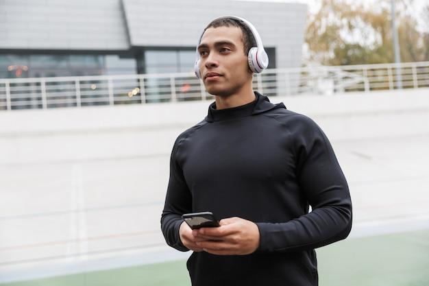 Wysportowany sportowiec rasy kaukaskiej w dresie używający słuchawek i telefonu komórkowego podczas treningu na stadionie po deszczu