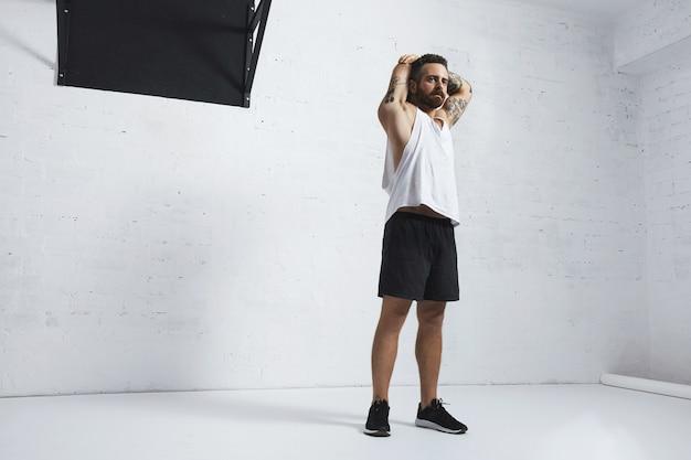 Wysportowany wytatuowany mężczyzna w białej koszulce pusty zbiornik rozciągający triceps na ramionach po treningu, na białym tle na mur z cegły