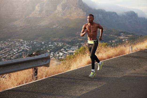 Wysportowany zdrowy człowiek biegnie wzdłuż drogi na zewnątrz, pokonuje duże odległości, przygotowuje się do maratonu. sportowy mężczyzna ćwiczy z górki, nosi sportowe buty, legginsy, jest w dobrej formie