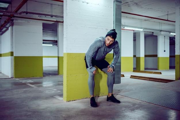 Wysportowany, zmęczony kaukaski sportowiec w aktywnym stroju odpoczywającym od biegania. wnętrze garażu podziemnego. nocna pora. koncepcja życia miejskiego.