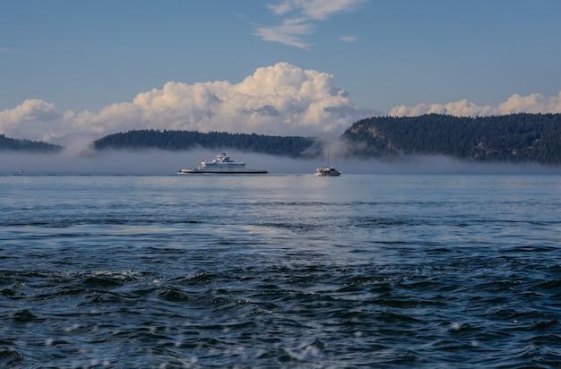 Wyspy i prom morski spowija mgła.
