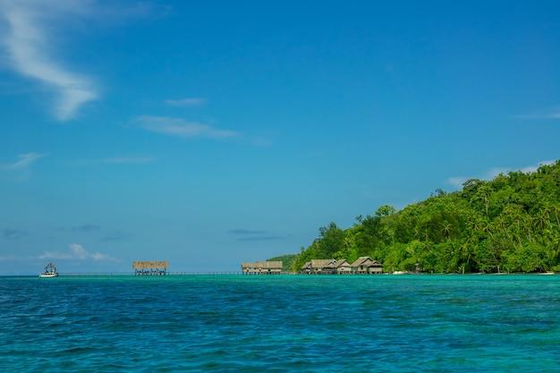 Wyspy indonezyjskie. niebieskie niebo. wybrzeże oceanu i dżungli. chaty na palach w wodzie