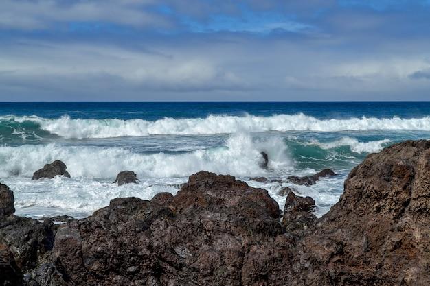 Wyspy kanaryjskie na oceanie atlantyckim. fale na czarnym skalistym wybrzeżu wulkanicznej teneryfy.