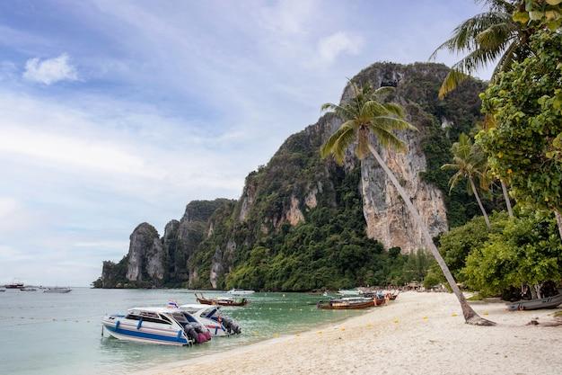 Wyspy phi phi z tropikalnym morzem andamańskim, wapienną górą i łodzią zakotwiczoną na plaży w krabi, tajlandia