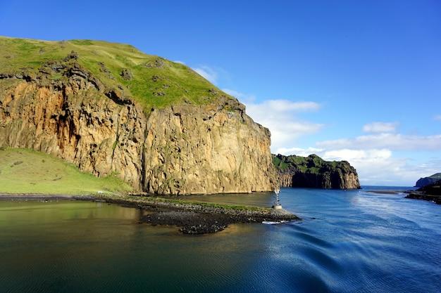 Wyspy westmana, vestmannaeyjar latem. zielona trawa i mech na szczycie klifów pobliskich gór.