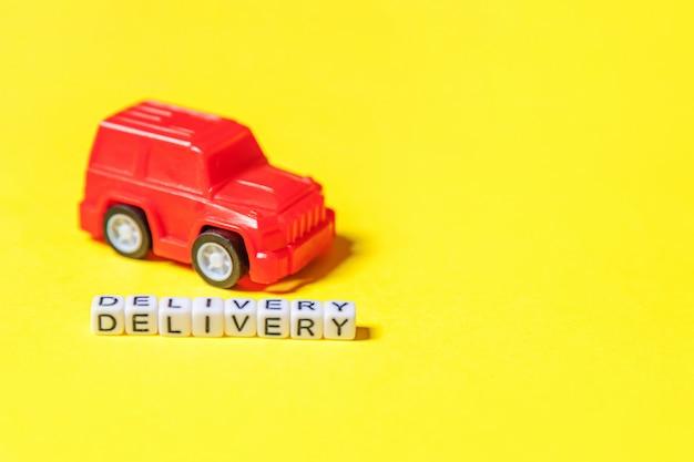 Wystarczy zaprojektować czerwony samochodzik i napis dostawa słowo na białym tle na żółtym tle kolorowe