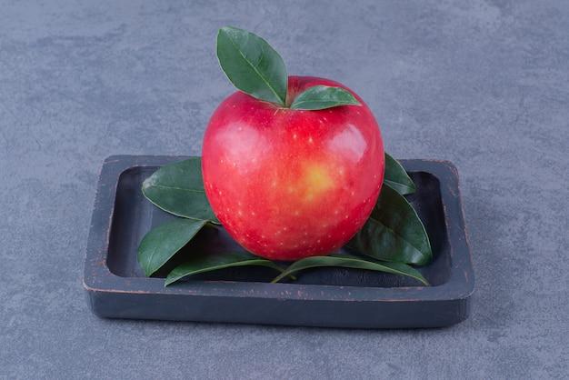 Wystawa jabłek na drewnianym talerzu na marmurowym stole.