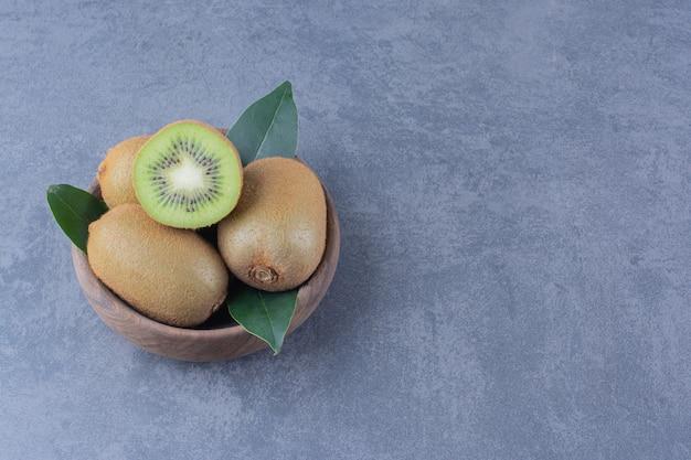 Wystawa owoców kiwi w misce na marmurowym stole.