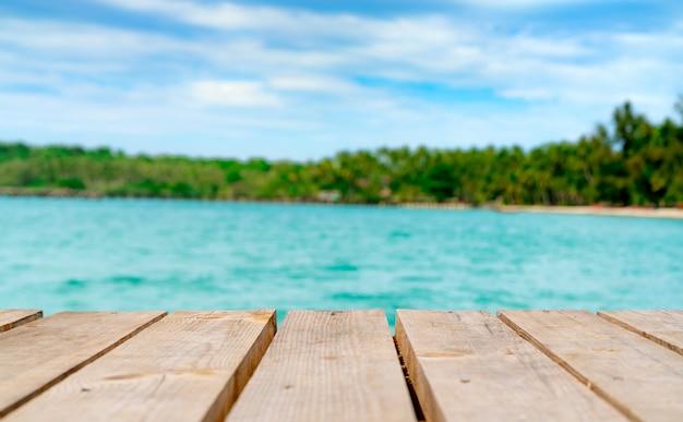 Wystawa produktów na letnią promocję. drewniany most na niewyraźne wody, drzewa kokosowego i piaszczystej plaży. pusta przestrzeń do montażu wyświetlacza produktu.