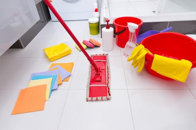 Wystawa różnorodnych produktów czyszczących na czystej białej podłodze wyłożonej kafelkami w łazience ze ściereczkami, gąbkami, mopem, wiadrem, umywalką oraz różnymi chemikaliami i detergentami