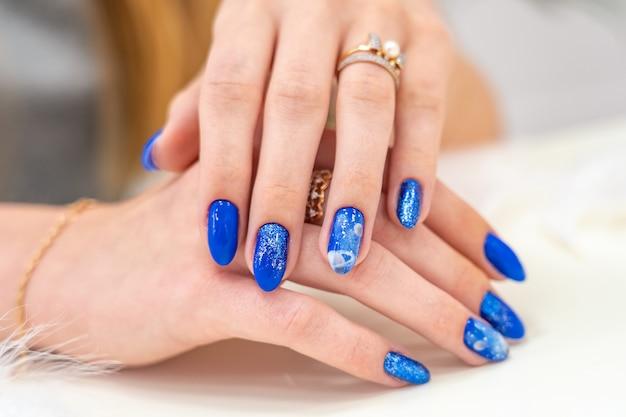 Wystawione są ręce dziewczyny z pięknym niebieskim manicure. niebieski błyszczący lakier do paznokci