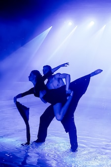 Występ na wodzie zespołu tanecznego na tle klubowego światła.