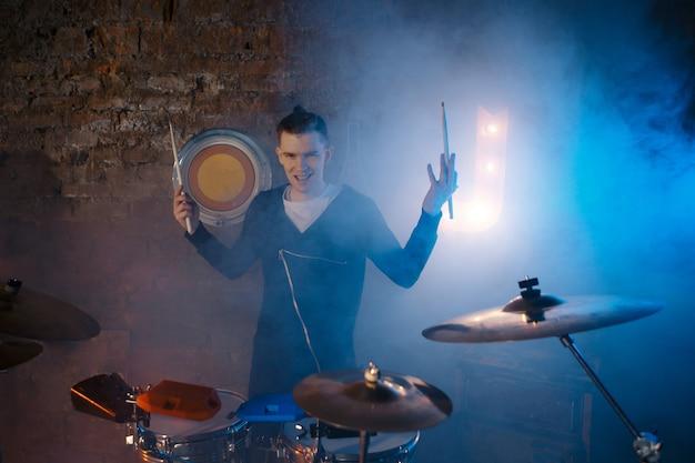 Występ zespołu rockowego. gitarzysta gra solo. basista gra solo. perkusista. bęben basowy. zbliżenie.