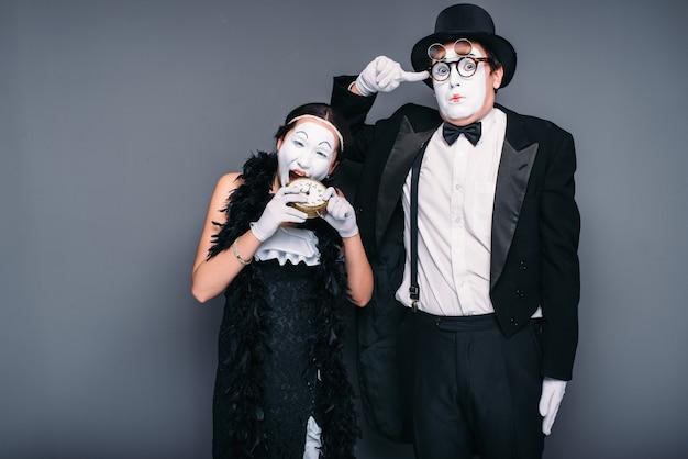 Występujący aktorzy mimowi, aktorka skubiąca budzik. wykonawcy teatru pantomimy