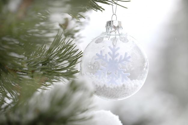 Wystrój choinki. ferie. piłka z płatka śniegu na gałęzi świerka na rozmytym jasnym tle