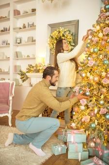 Wystrój domu młoda szczęśliwa para razem dekorowanie choinki