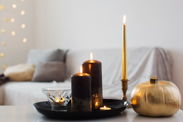 Wystrój domu ze złotą dynią i płonącymi świecami