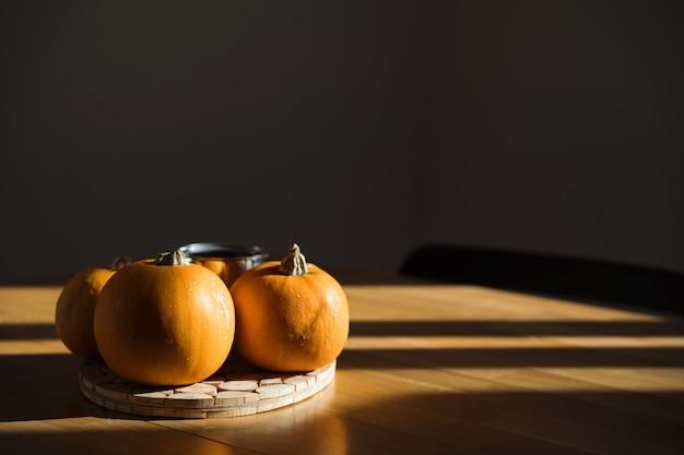 Wystrój dyni na drewnianym stole w domu w słońcu. cienie jesiennego słońca. halloween. wysokiej jakości zdjęcie