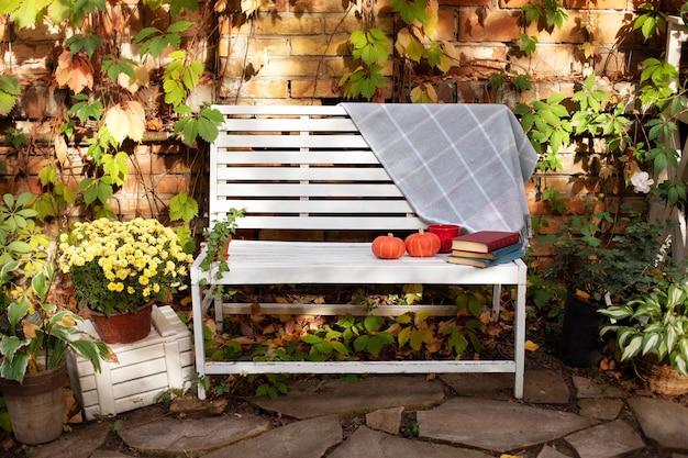 Wystrój jesiennego podwórka. biała ławka w jesiennym ogrodzie z roślinami i chryzantemą