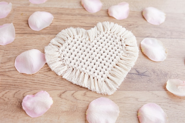 Wystrój makramy. walentynki. serce i płatki róż. naturalne materiały, bawełniana nić. ekologiczne dekoracje, ozdoby, ręcznie robiony wystrój na drewnianym stole