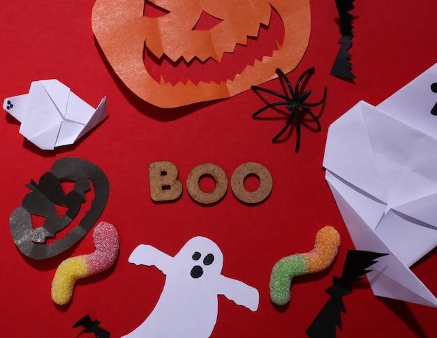 Wystrój papieru czerpanego halloween, gummy robaki i słowo boo na czerwonym tle. widok z góry