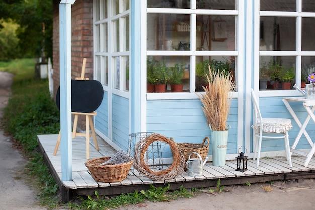 Wystrój podwórka wiejskiego domu. zielone rośliny i kwiaty na tarasie domu. wiklinowe kosze