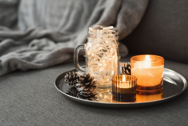 Wystrój salonu: dwie płonące świece zapachowe koloru pomarańczowego, szyszki i lampki choinkowe
