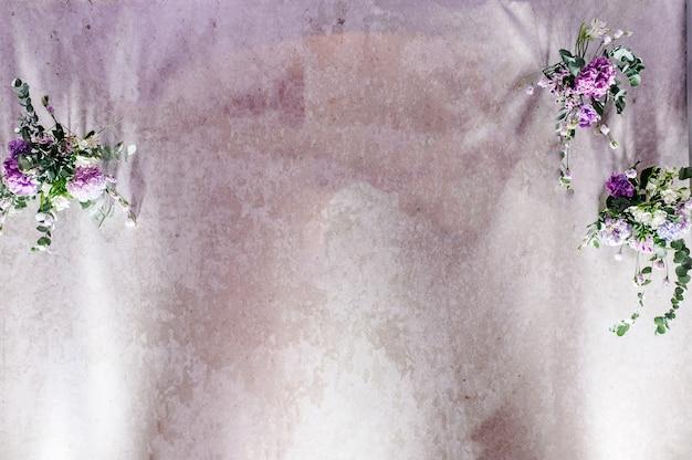 Wystrój ślubny. ściana ozdobiona kompozycją fioletowych, fioletowych, różowych kwiatów i zieleni w sali bankietowej. tło.