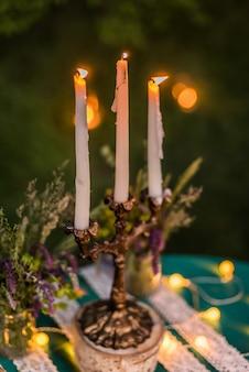 Wystrój ślubny, świece na stole, żarówki, szmaragdowozielony kolor