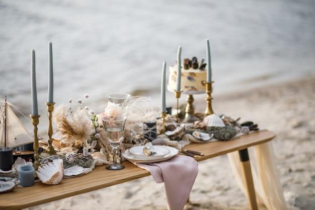 Wystrój ślubu morza na wybrzeżu. tort weselny i kwiaty na imprezie.