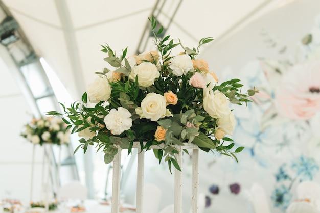 Wystrój stołów ozdobiony świeżymi kwiatami na uroczysty obiad, wesele
