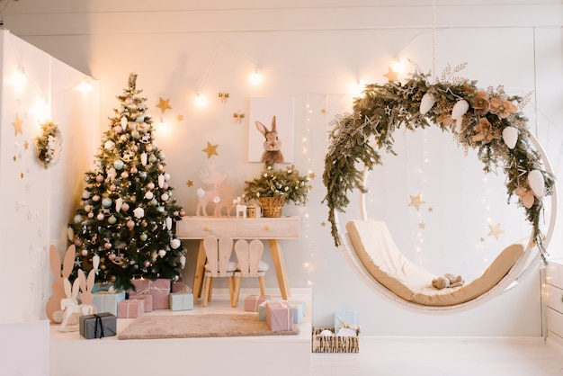 Wystrój świąt bożego narodzenia i nowego roku. wystrój pokoju dziecięcego z kleką, zabawkami i huśtawkami. drewniany stół i krzesło, selekcyjna ostrość
