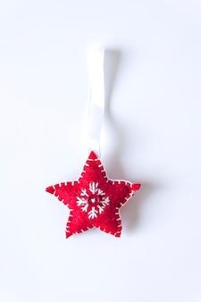 Wystrój świąteczny lub nowy rok. czerwona miękka gwiazda z haftem na białym tle