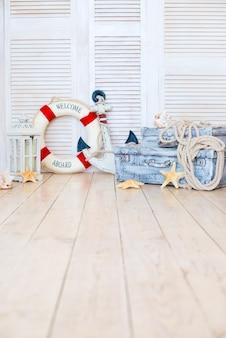 Wystrój w stylu morskich podróży, walizki i kotwica, koło ratunkowe, latarnia.
