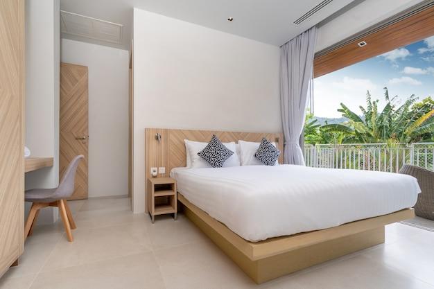 Wystrój wnętrz i elementów zewnętrznych w willi, domu, domu, mieszkaniu i apartamencie obejmuje łóżko w sypialni z widokiem na balkon