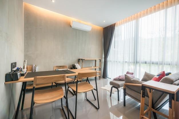 Wystrój wnętrz w salonie z biurkiem i rozkładaną sofą oraz jasną przestrzenią