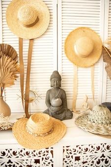 Wystrój wnętrza w jasnych kolorach, na półce posąg buddy, na ścianach wiszą słomiane kapelusze