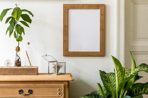 Wystrój wnętrza z drewnianą komodą vintage, brązową ramką na zdjęcia, rośliną awokado, rośliną i eleganckimi dodatkami osobistymi.