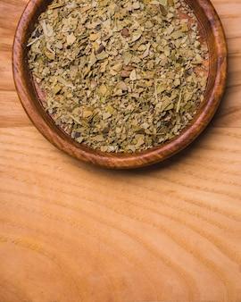 Wysuszeni herbaciani liście na talerzu nad drewnianym tłem