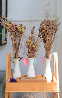 Wysuszeni kwiaty w wazowej dekoraci na drewnianej półce przy kawiarnią.